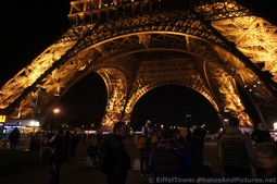 People gather at the base of the Eiffel Tower at night.jpg